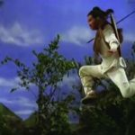 Video still of a martial arts man in the air about to land on the ground. There are trees in the background.