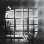 Black and white photograph of a window in the foreground and the view of industrial buildings in outside of the window.