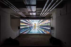 A video installation showing a woman in a supermarket. The screen is in a basement with speakers at either side and exposed pipes on the ceiling.