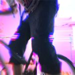 Pink distorted background, in the foreground there is a close-up of someone on a bike. Upper body of the person is not shown