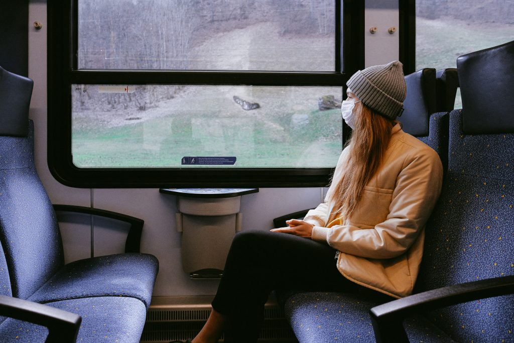 a woman with long hair sits in a train carriage looking out of the window