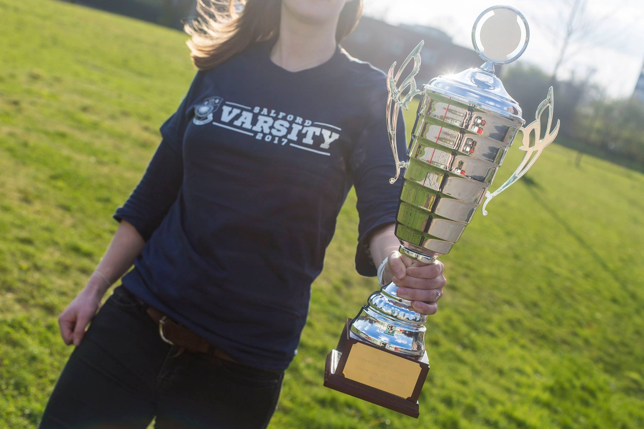 A picture of someone holding the Varsity Trophy