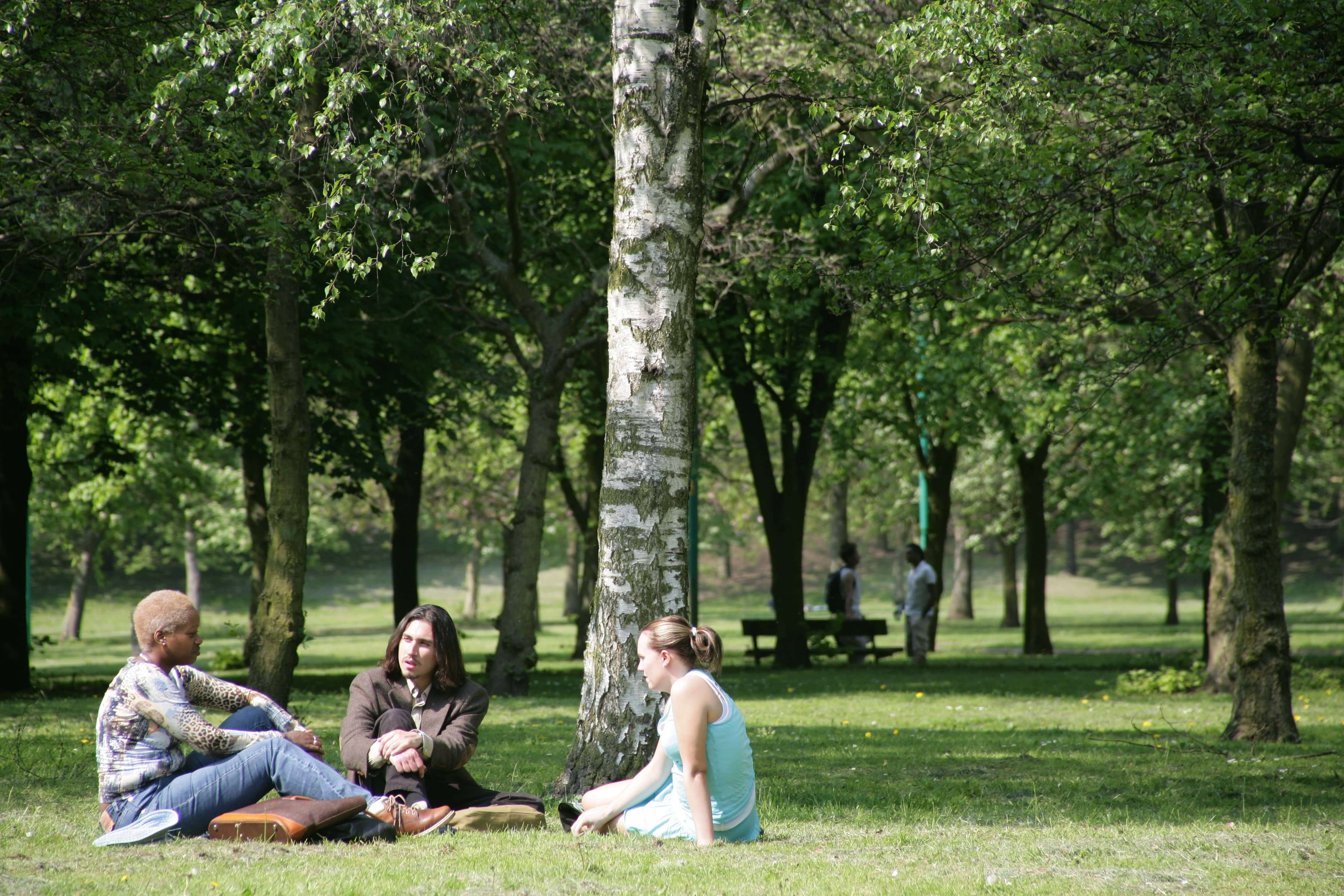Students sitting within Peel Park, Salford