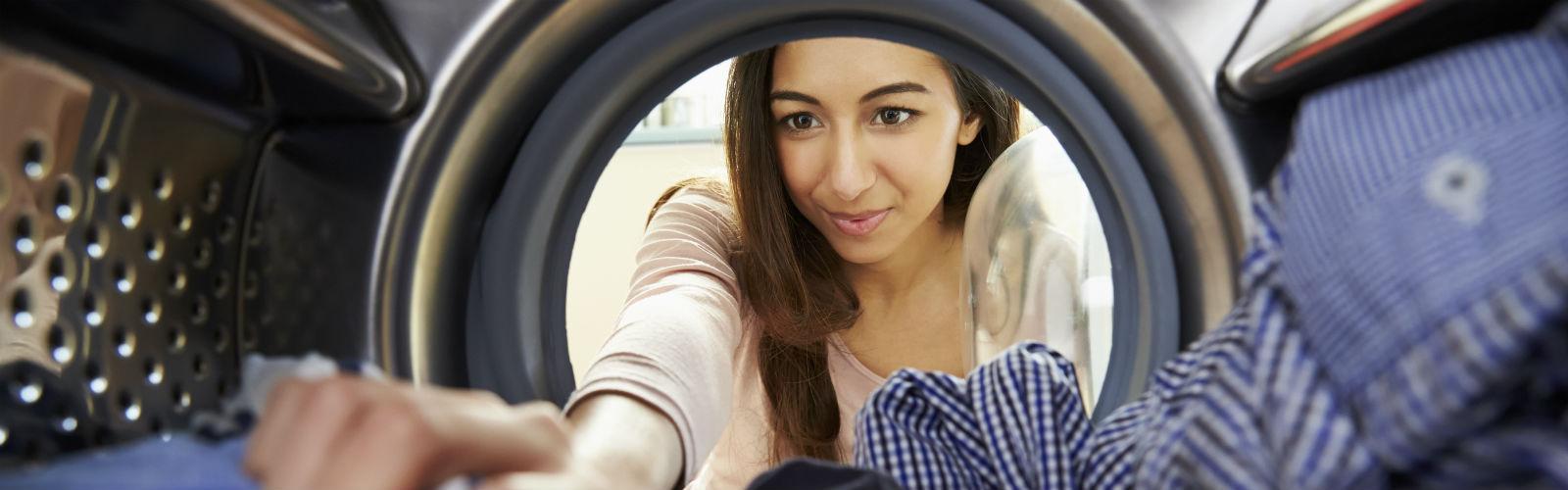 Woman loads washing into a washing machine