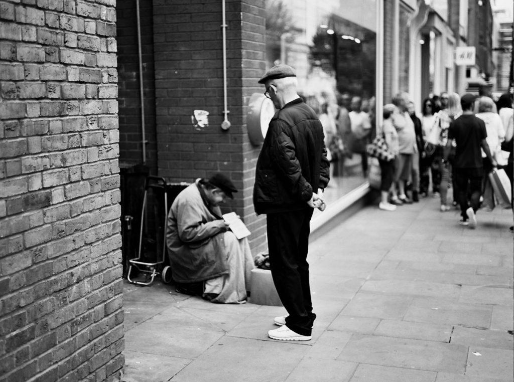 Image: Man looking at homeless man