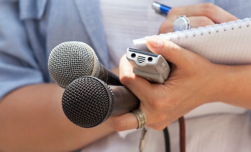 Journalist holding microphones and notepad