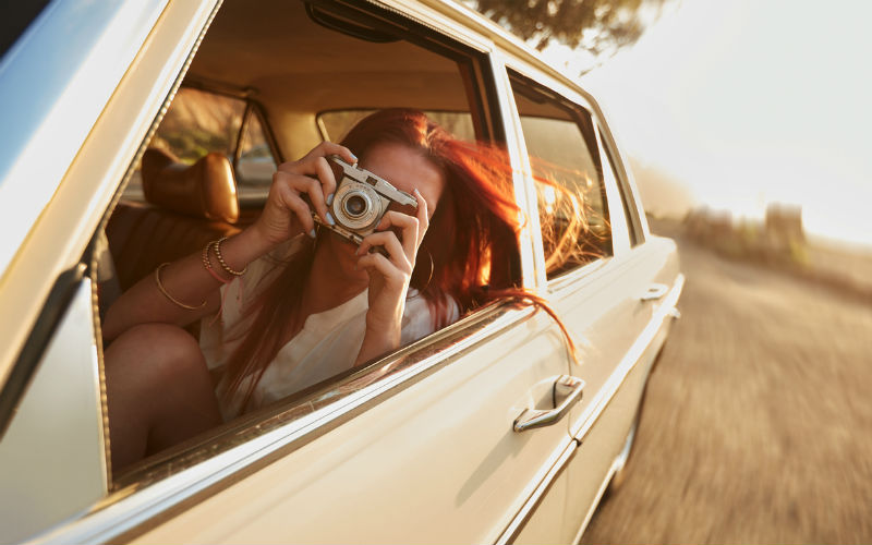 A girl taking photos from a car