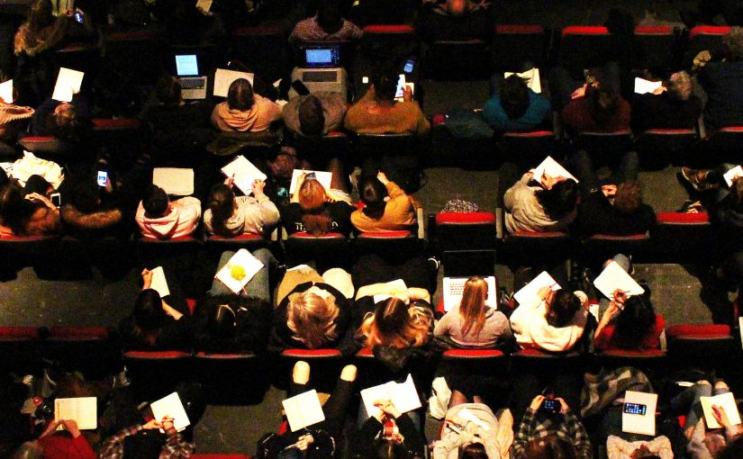 Birdseye view image of students making notes at the conference
