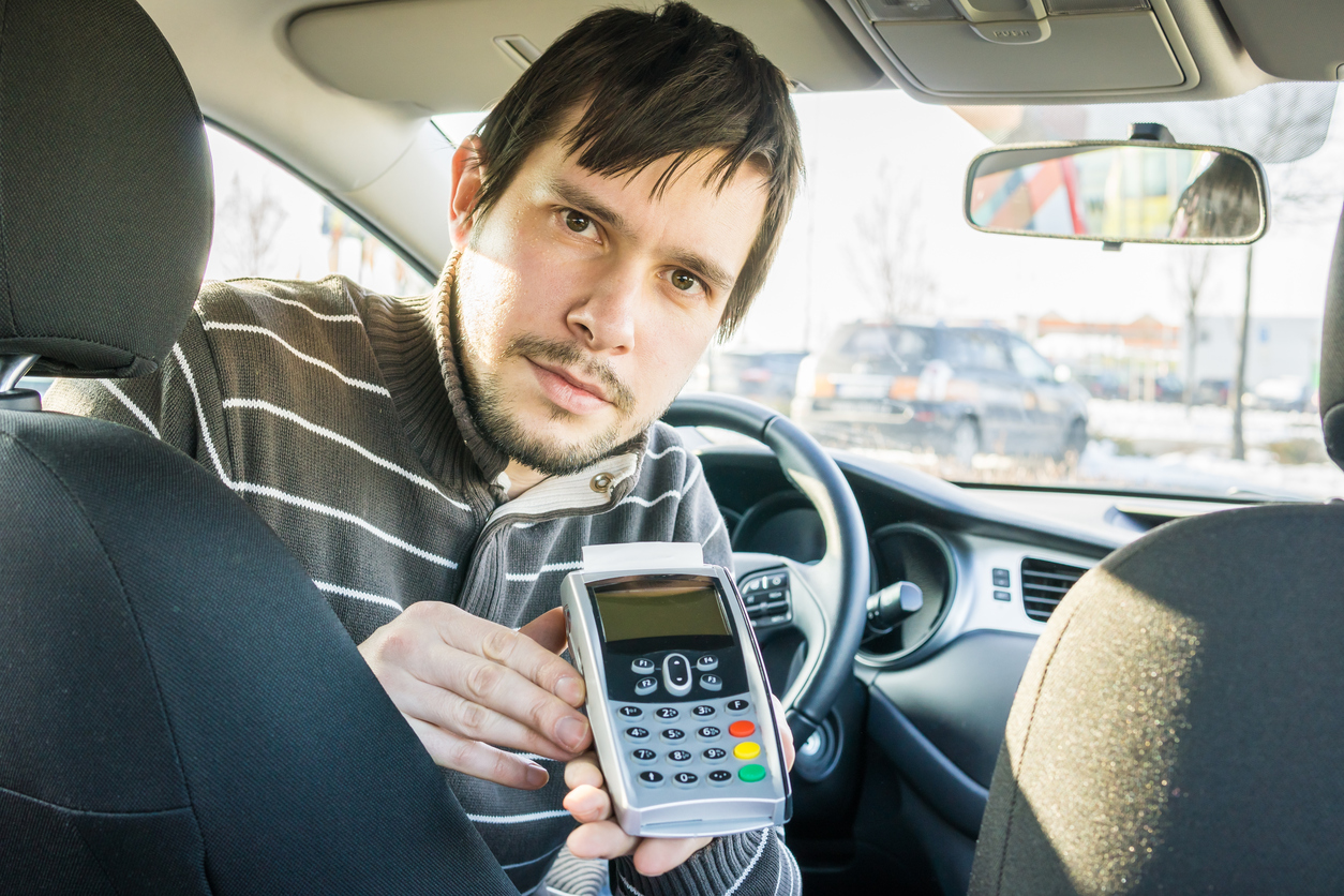 Image: Man ready to accept card payment in a car