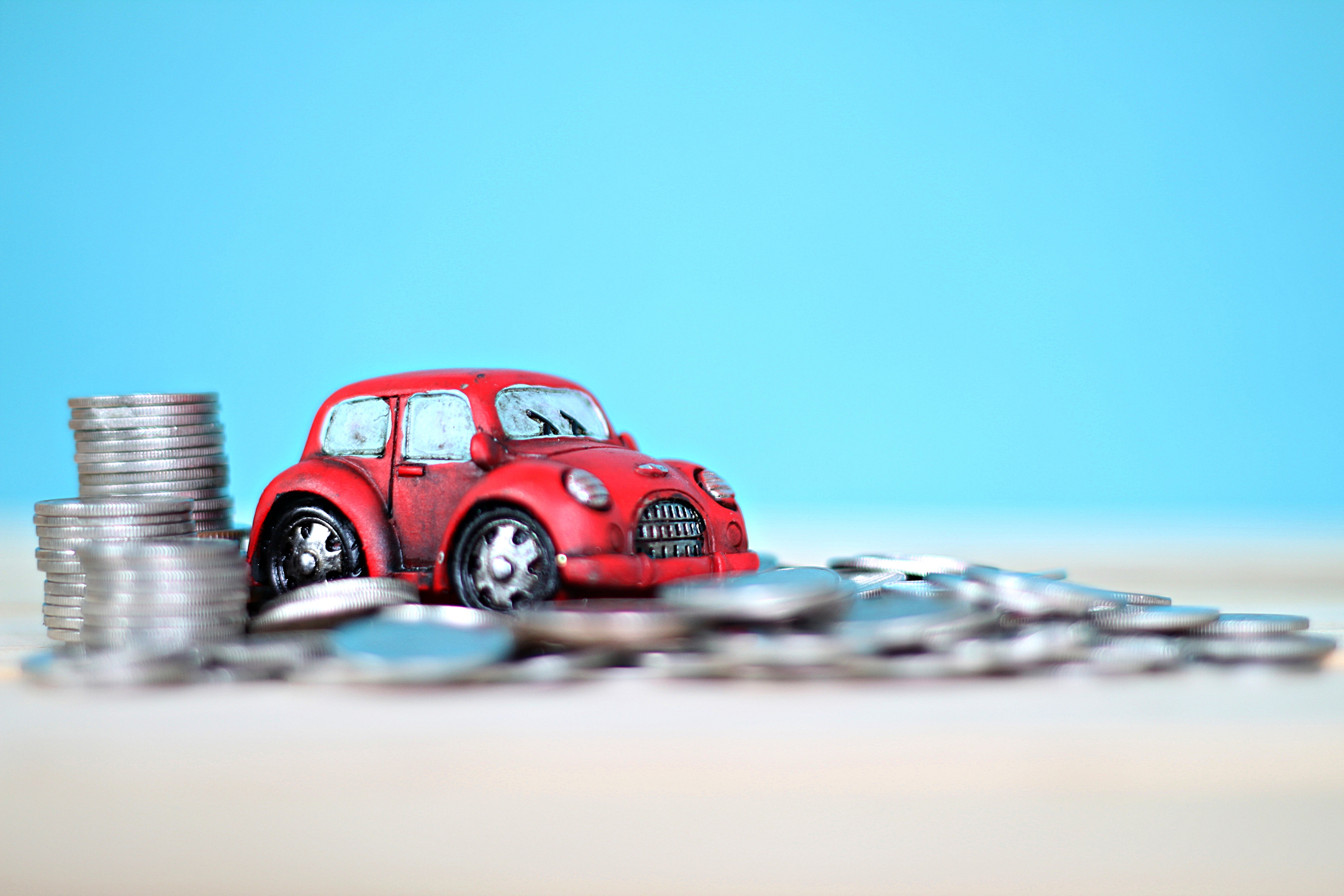 Image: Toy car driving over a pile of money.