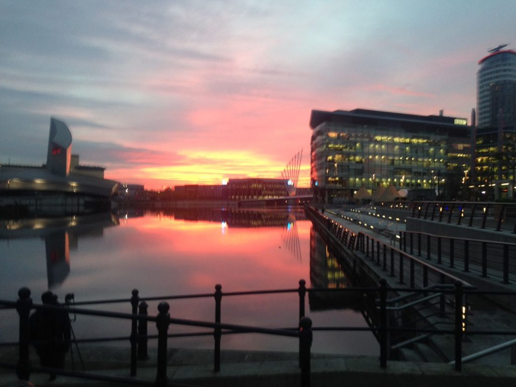 Image: this is a photograph of the sun setting in Salford Quays.