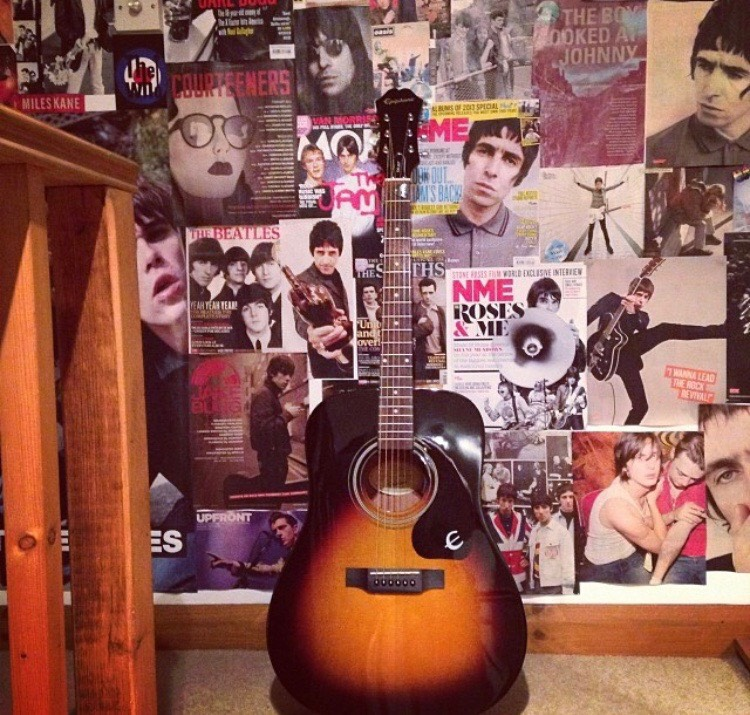 Image: Guitar against wall covered in NME magazine cut-outs indie/alternative music