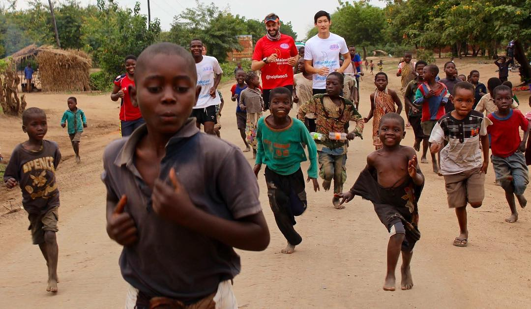 image: salford graduate running with children of malawi africa