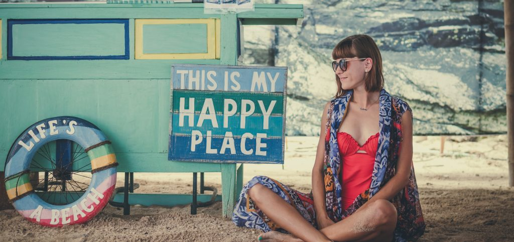 "Lady sitting on the beach with a sign that reads ""this is my happy place"" and ""life's a beach"""