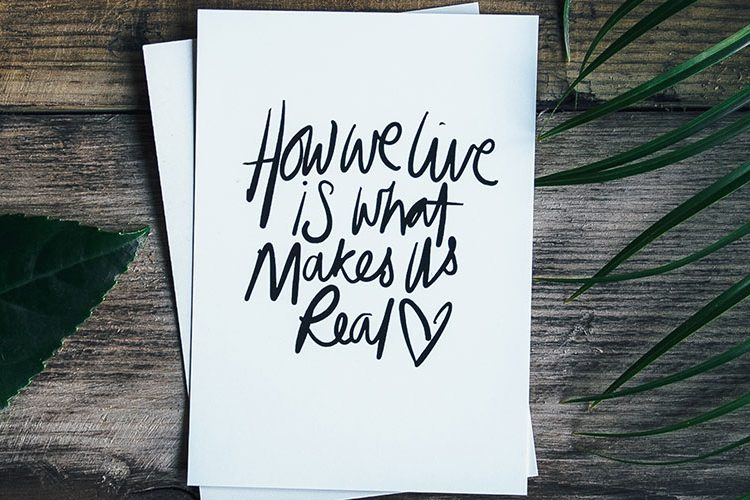 "Image: Card with ""How we live is what makes us real"" text"