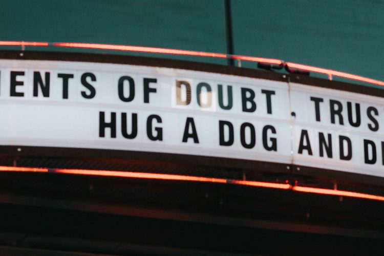 Old fashioned theatre sign reading: In moments of doubt, trust your gut, hug a dog and drink gin
