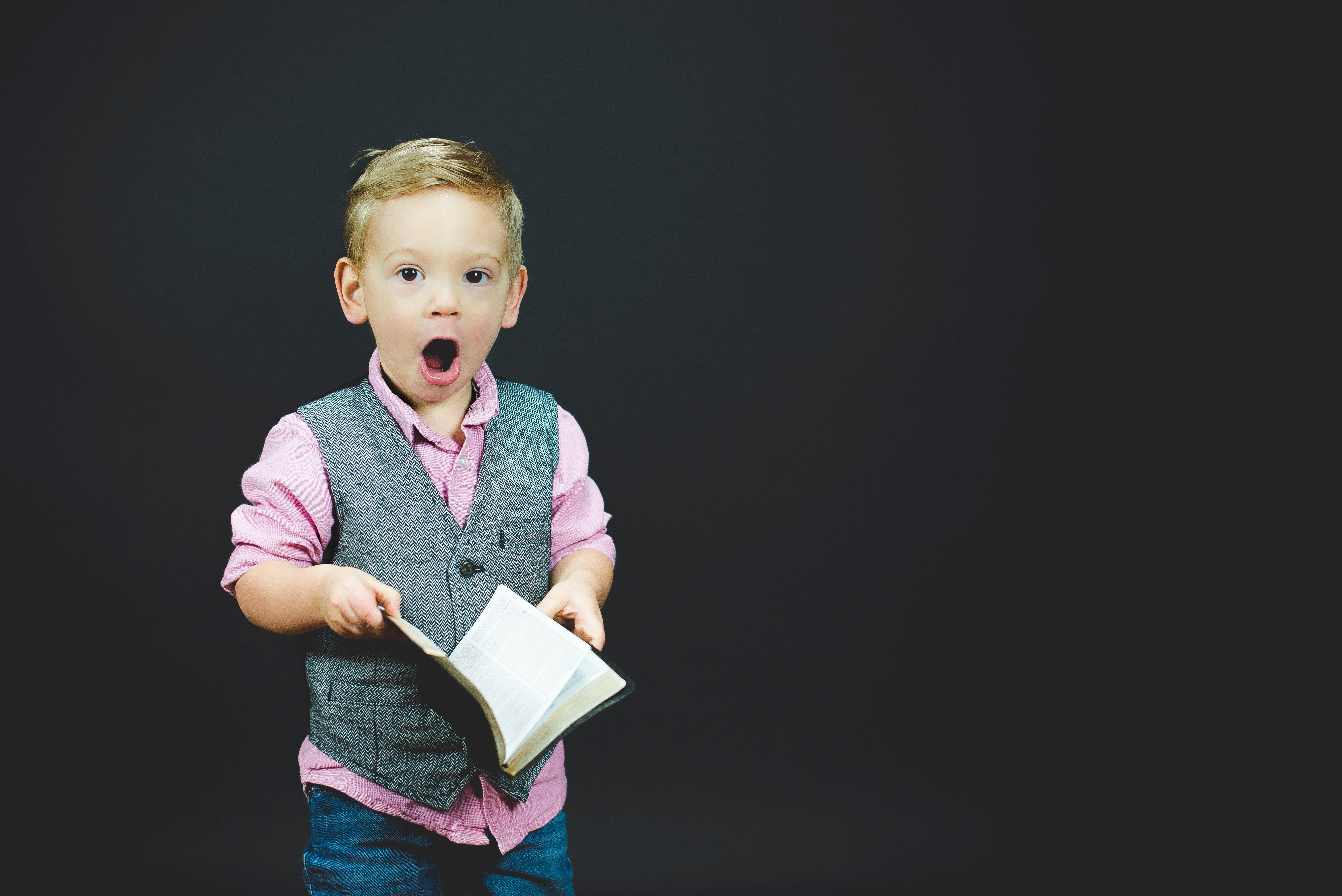 A little boy against a black background holding a book