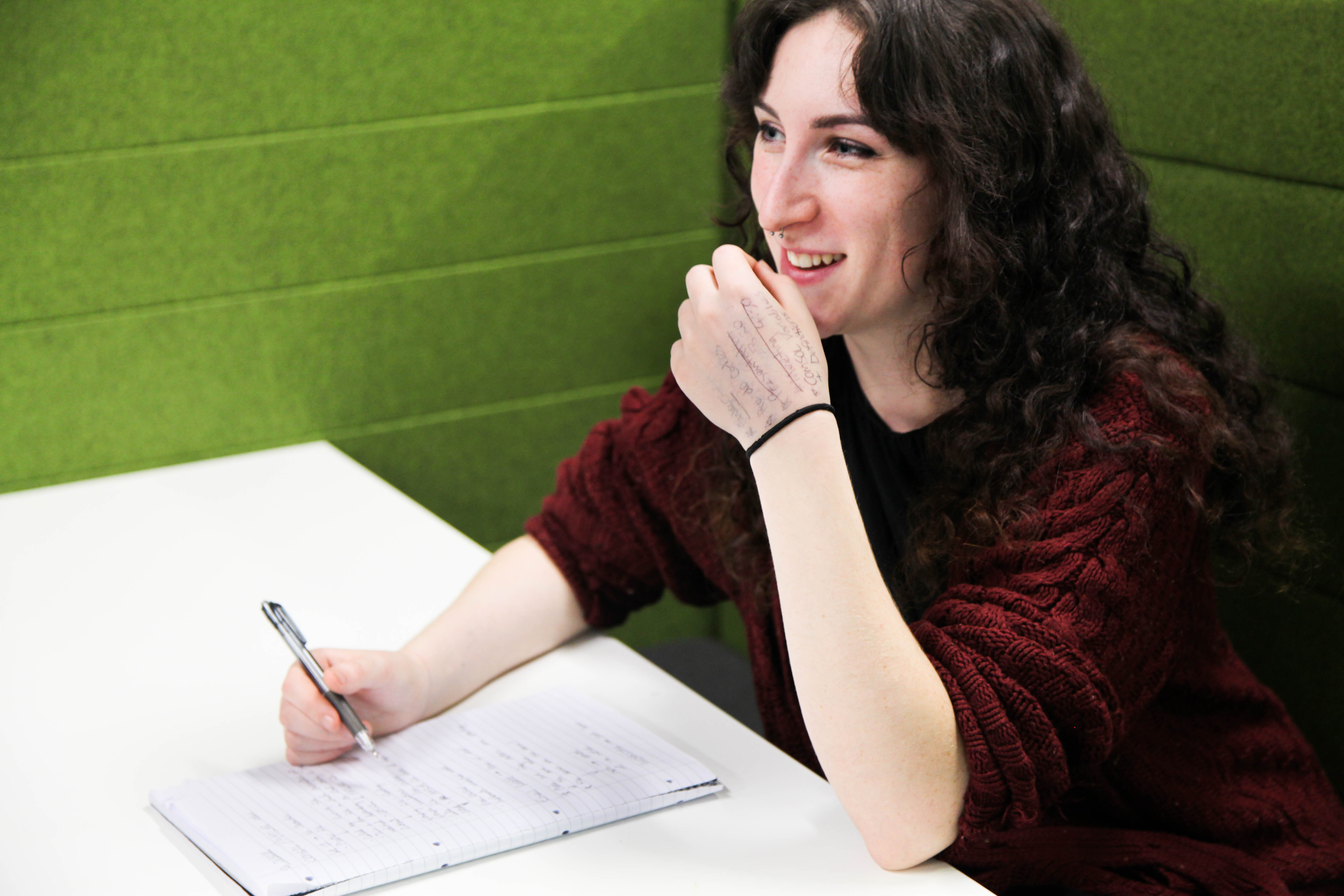Image - Student smiling whilst writing at table.