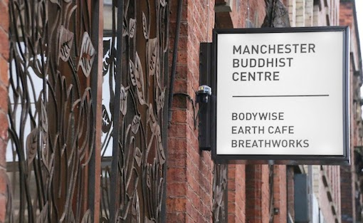 This photo shows the side of the Manchester Buddhist Centre's exterior, which has a white square sign coming off the wall that says 'Manchester Buddhist Centre. Bodywise, Earth Cafe, Breathworks'.