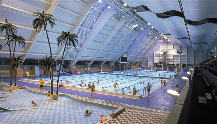 This shows a wide shot of the swimming pools located in the Manchester Aquatics Centre. There are plenty of people swimming and you can see that it has plenty of different lanes, fake palm trees and equipment.