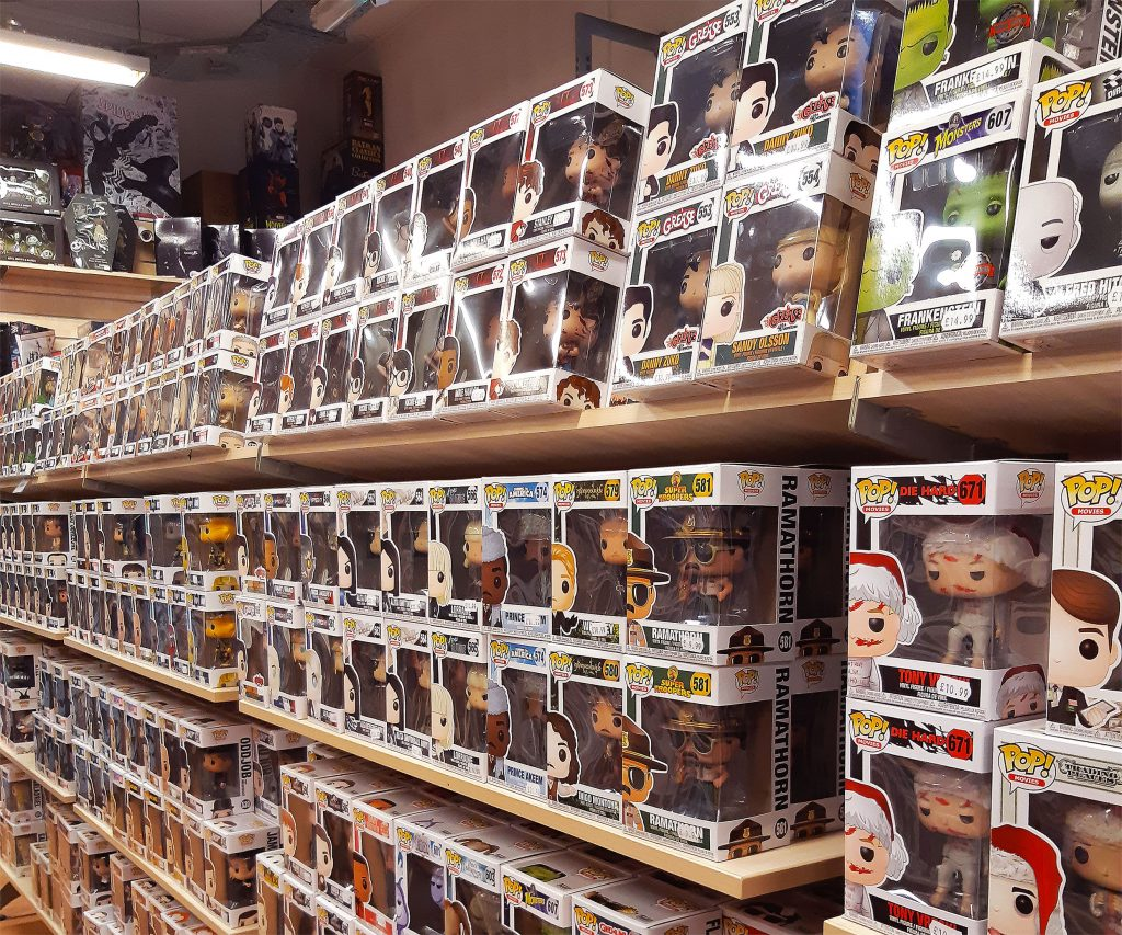 Three rows of wooden shop shelves in the Forbidden Planet Manchester store which are full of Funko Pop Vinyl figures new in their boxes. Nearest to the camera you can see characters from series such as Grease and Die Hard.