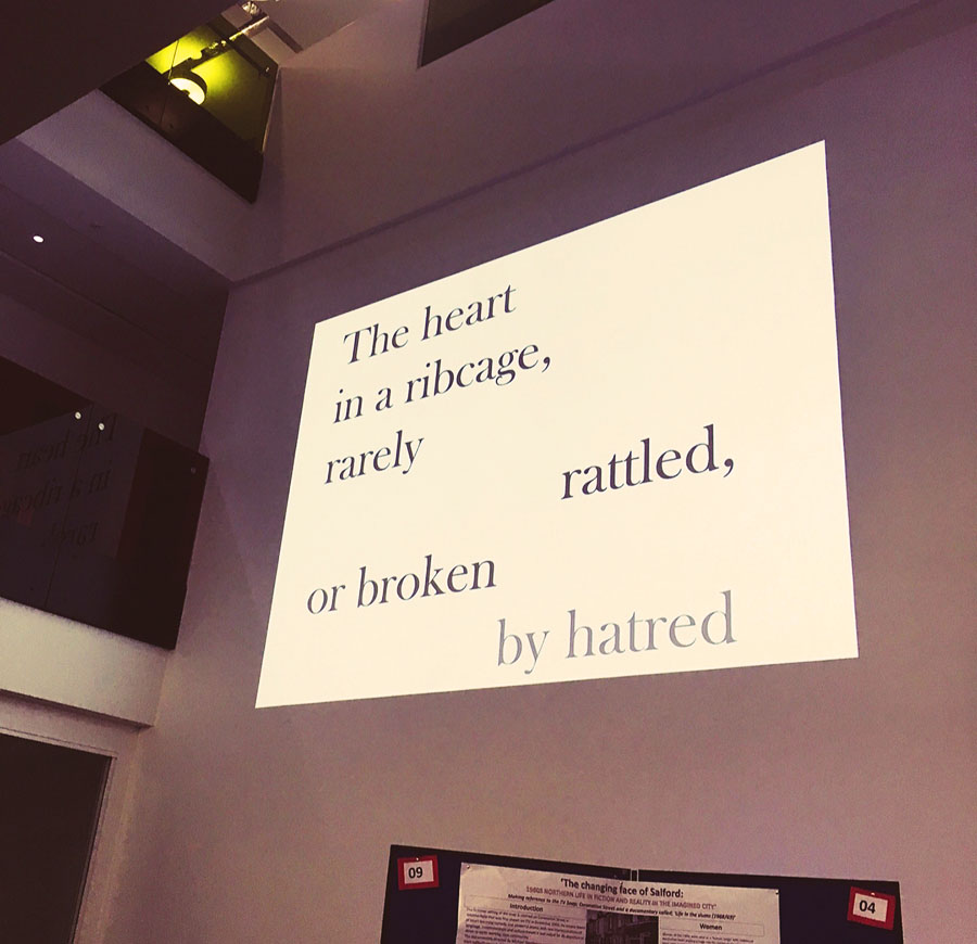 There is a presentation projected onto a blank wall in the University of Salford's MediaCityUK campus. On the projection is some visual poetry spaced out. It reads 'The heart in a ribcage, rarely rattled, or broken by hatred.'