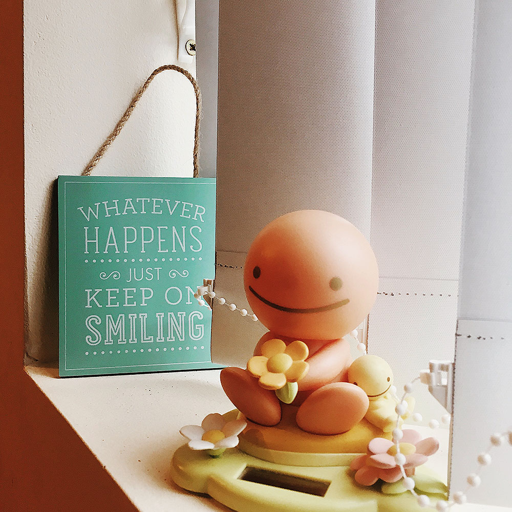 A small wooden hanging that says 'Whatever happens just keep on smiling' next to a solar powered 'Sun Buddy' bobble head.
