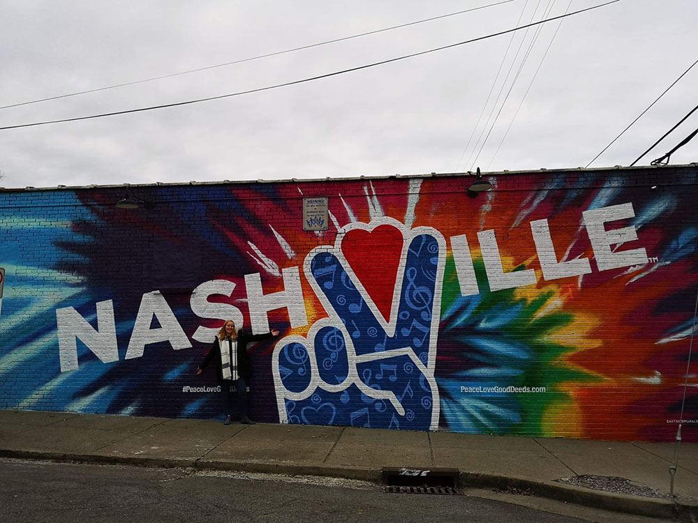 Incredible street art/mural in Music City, Nashville with a peace sign on and a rainbow effect in the background.