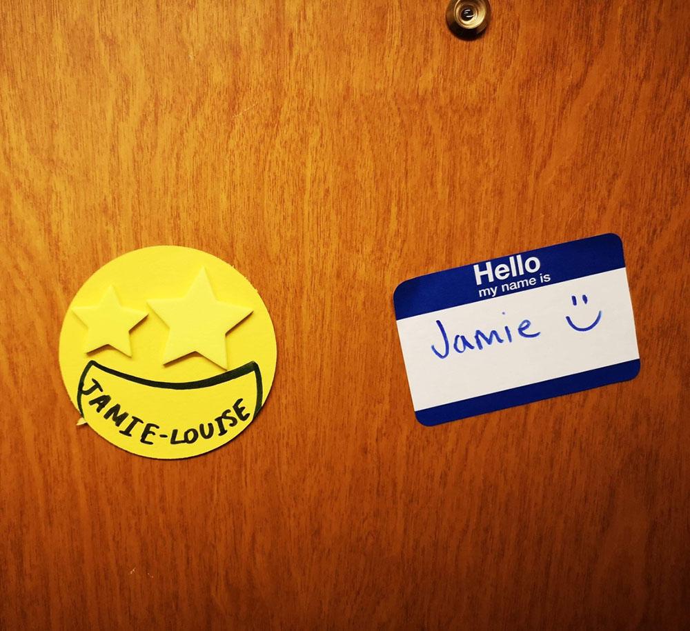 Stickers on a wooden door, one is in a yellow circle shape with stars for eyes and the name 'Jamie-Louise' penned on. The other sticker is a typical 'Hello my name is' sticker with 'Jamie' and a smiley face drawn in the white center.