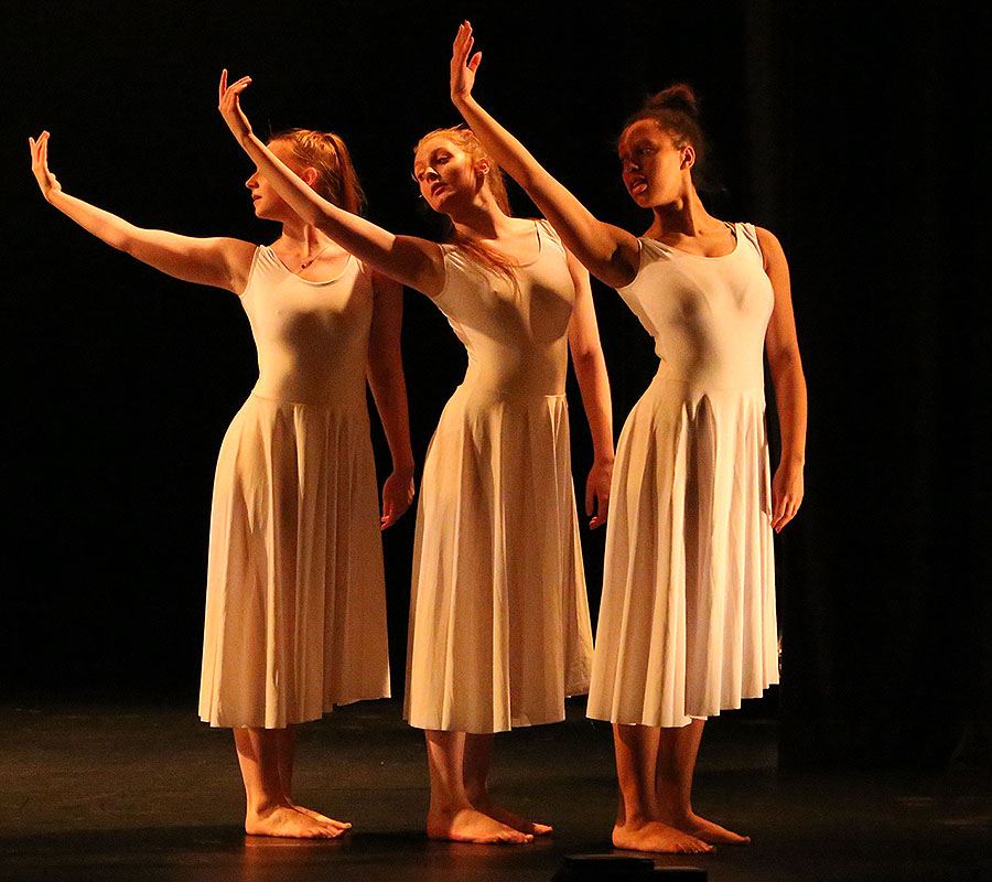 Three of our University of Salford Dance students performing in a warm light on the New Adelphi Theatre stage. In unison the girls are raising their right arms during their dance performance.