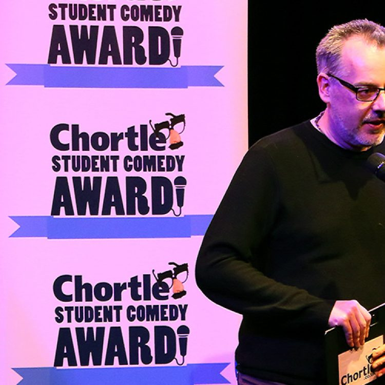 Steve Bennett, manager of chortle hosting on the main stage in front of two flats with the 'Chortle Student Comedy Awards' logos on