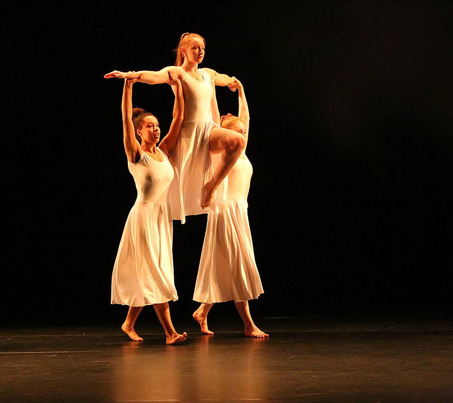 The three Salford dance students performing in a warm light. Two of the girls have the other held up high above their shoulders.