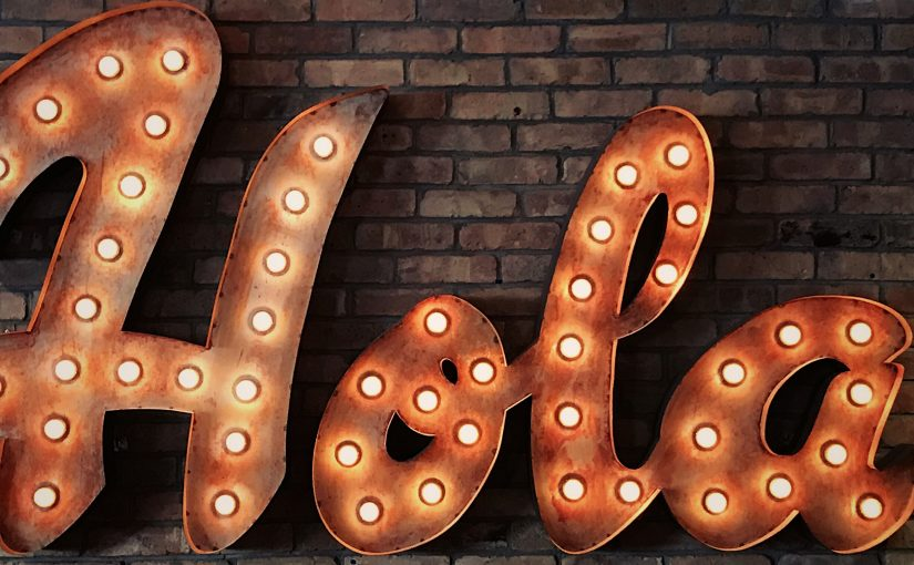 the word 'Hola' in lights on a brick wall