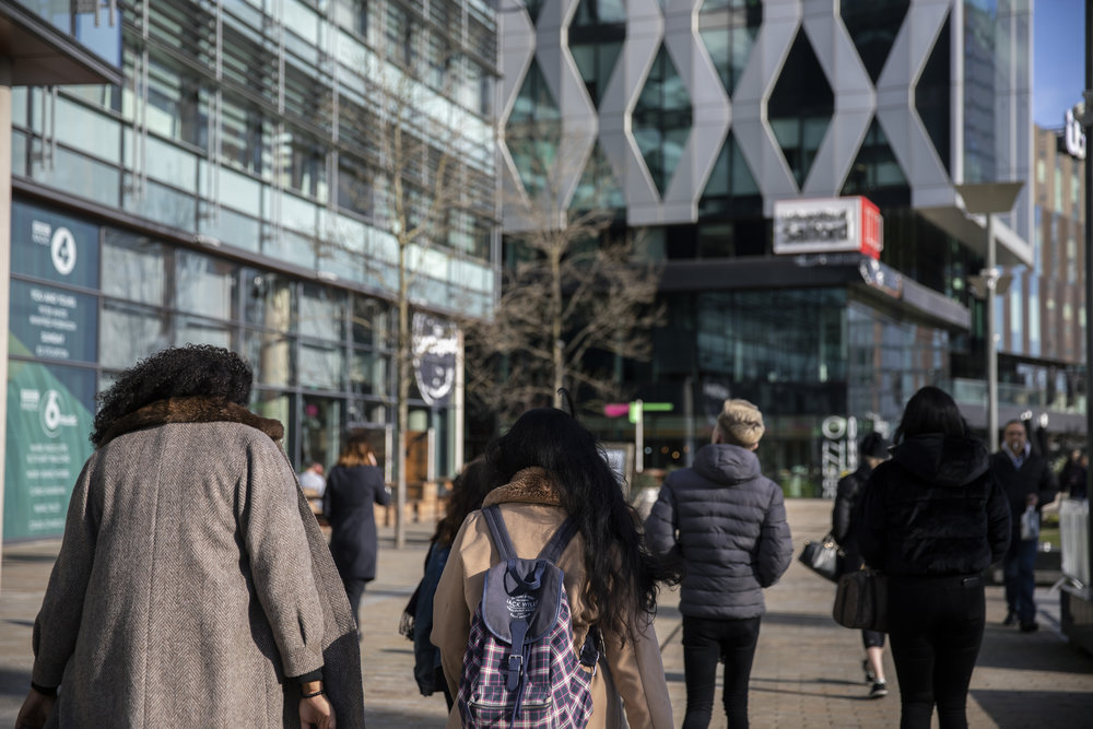 A shot of several students walking towards the University of Salford building in MediaCityUK.
