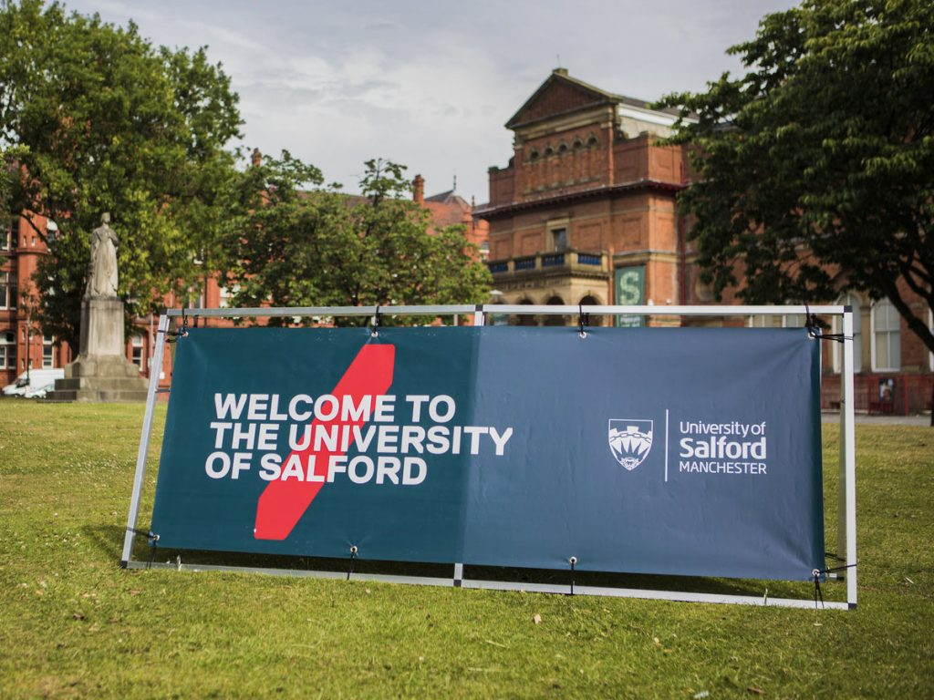 In the background is the Salford Museum and Art Gallery as well as some fully bloomed trees, a statue and green grass. In the foreground is a horizontal sign with our logo on and the words 'Welcome to The University of Salford'.