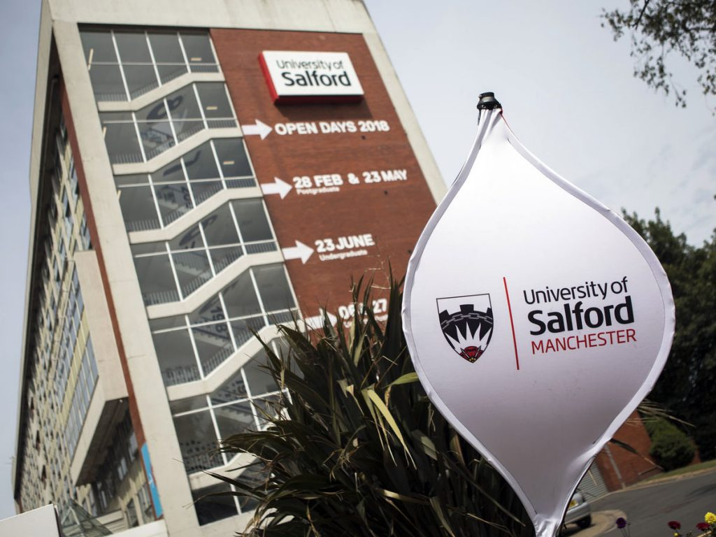 In the background is the Maxwell Building with each 2018 open day written alongside the windows. In the foreground is a plant and a spinning sign that reads 'University of Salford Manchester'