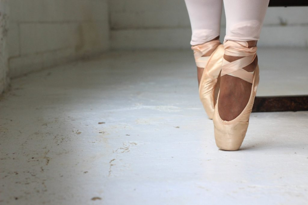 A close up of someone's feet in ballet pumps performing pointe.