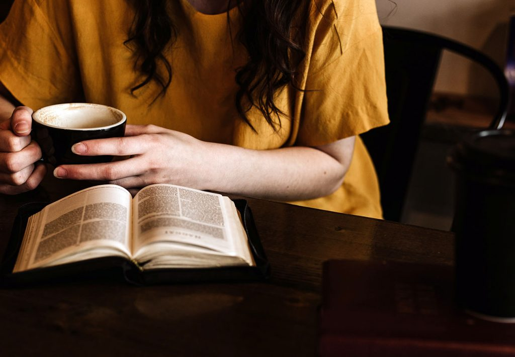 Sat on a dark wooden table is a cup, a book and an opened book that a person is reading. This person wears a mustard yellow t-shirt and has long dark hair. You cannot see their face. They are drinking from a black cup of coffee.