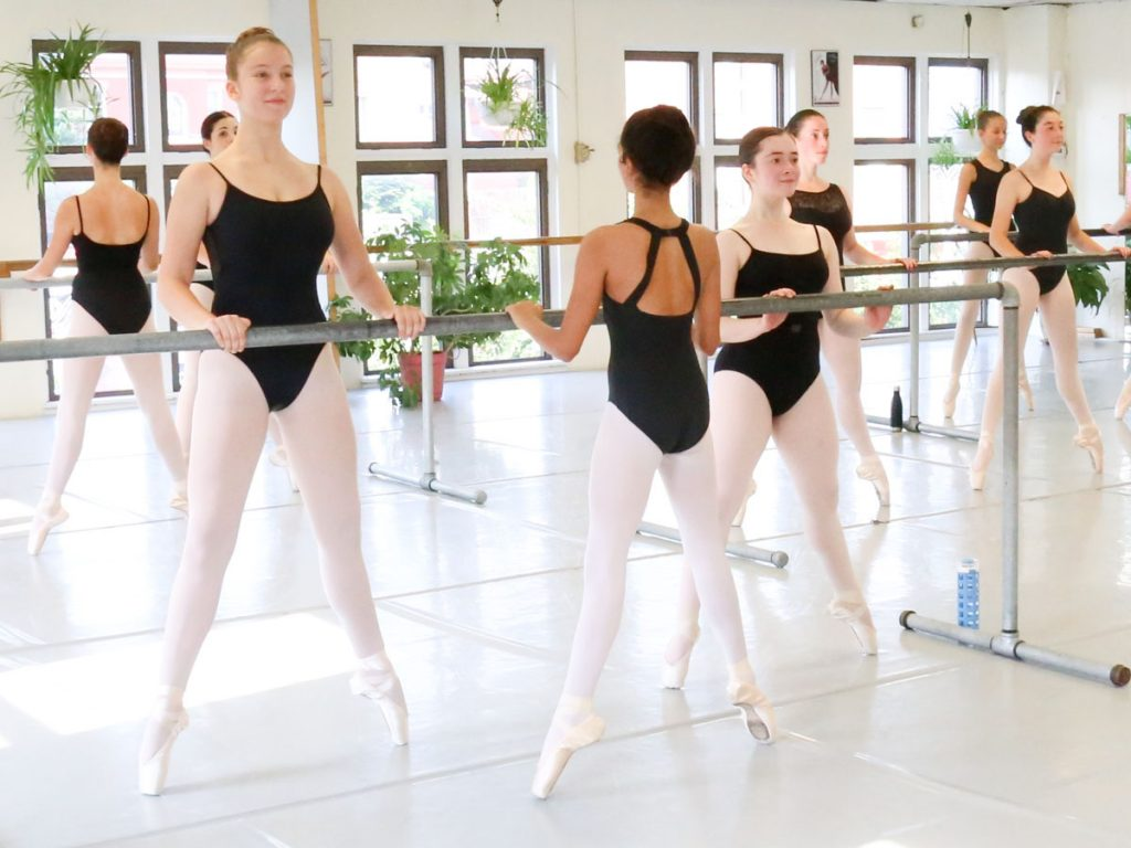 Dancers in black leotards and white tights practicing on barres