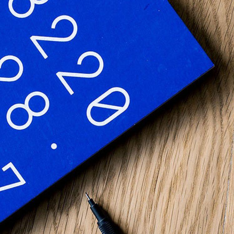 An up close shot of a laptop and a blue notebook