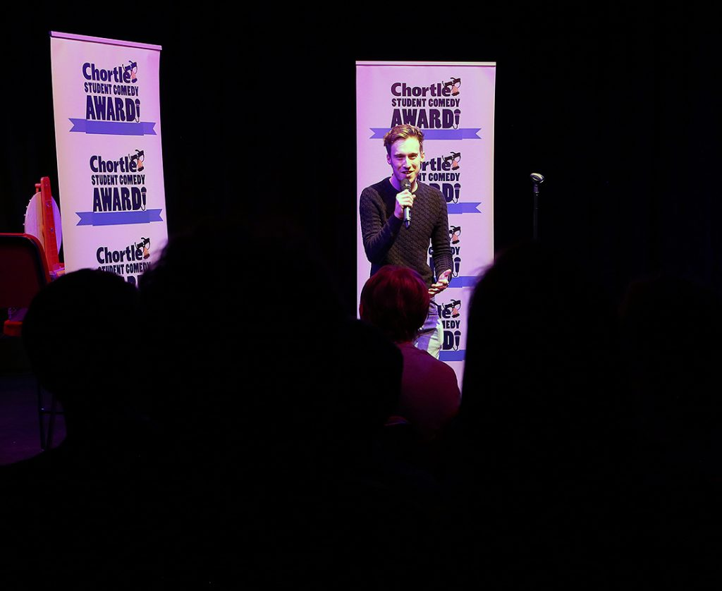 Callad Gale wearing a dark grey jumper performing in front of a big crowd. He is stood in front of two flats with the Chortle Student Comedy Award logos on it.