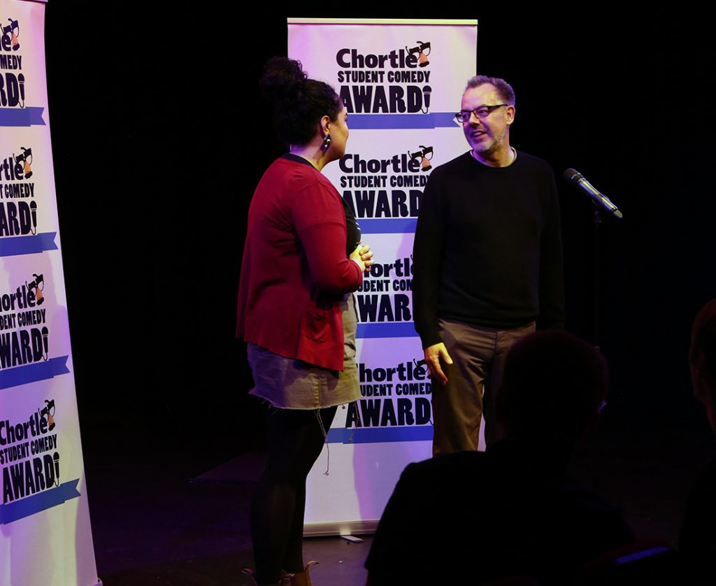 After being announced winner of the Student Comedy Awards, this photo shows Chortle manager Steven Bennett and winner Erika Ehler stood on the stage in front of the microphone talking with the Chortle Student Comedy Award logos behind them