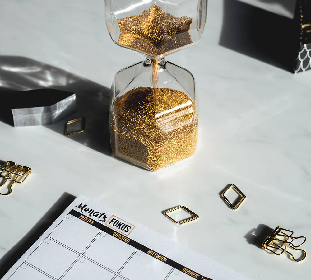 A close up of a white desk that has a sand timer on it with vibrant gold sand. As well as the time there is gold paper clips and binder clips and a desk calendar.