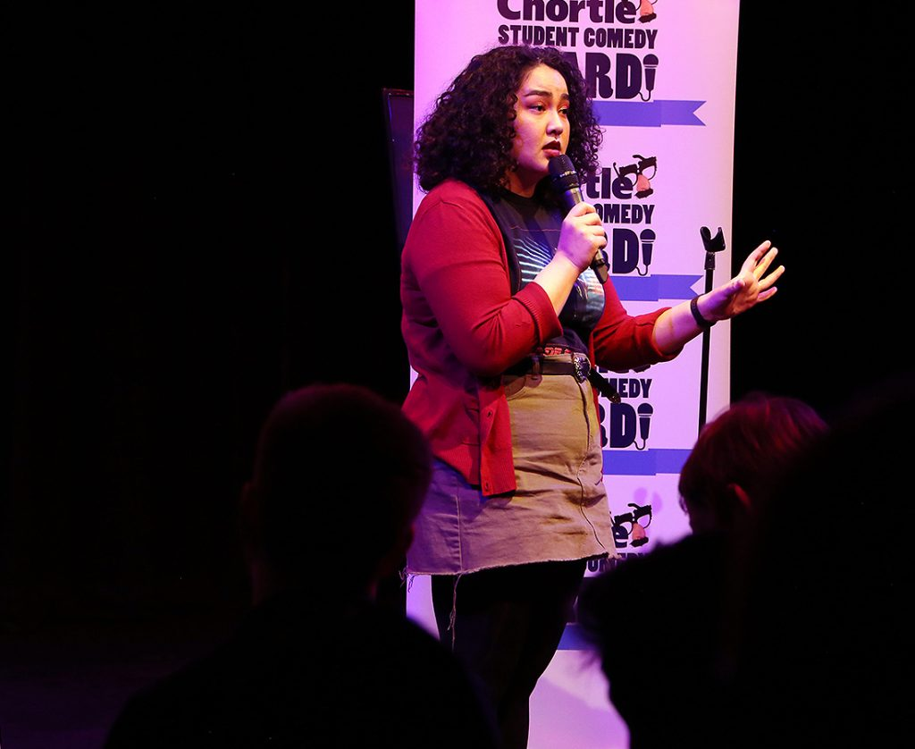 Erika Ehler wearing a red cardigan and khaki skirt, mid-speech performing in front of the crowd. She is holding the microphone and stood in front of one of the flats with the 'Chortle Student Comedy Award' logos on.