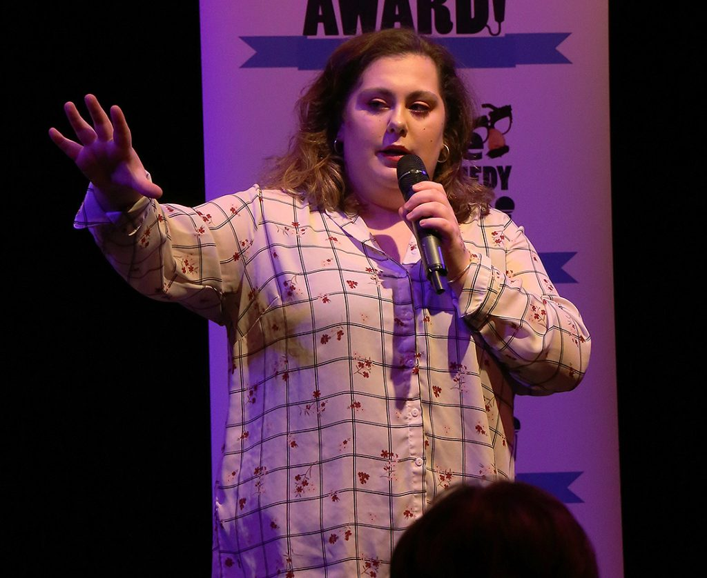 Maisy Whipp wearing a white checkered shirt with flowers on performing in front of the crowd. She is mid-speech and holding the microphone.