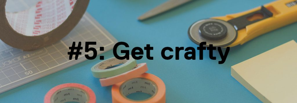 Photo by Jo Szczepanska on Unsplash. In the background you can see on a blue table there is several craftwork tools such as a cutting board, different coloured paper tapes, a big role of brown packing tape, some scissors, a post it note and a cutting tool. In the foreground the text reads '#5: Get crafty'