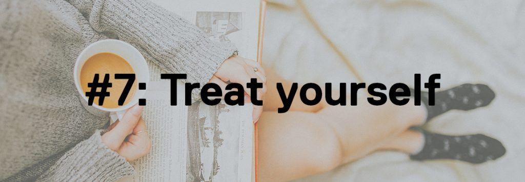 Photo by Anthony Tran on Unsplash. In the background image is a girl in a grey jumper and dark blue socks with a book on her lap whilst in one hand she carries a cup of tea. The foreground text says '#7: Treat Yourself'