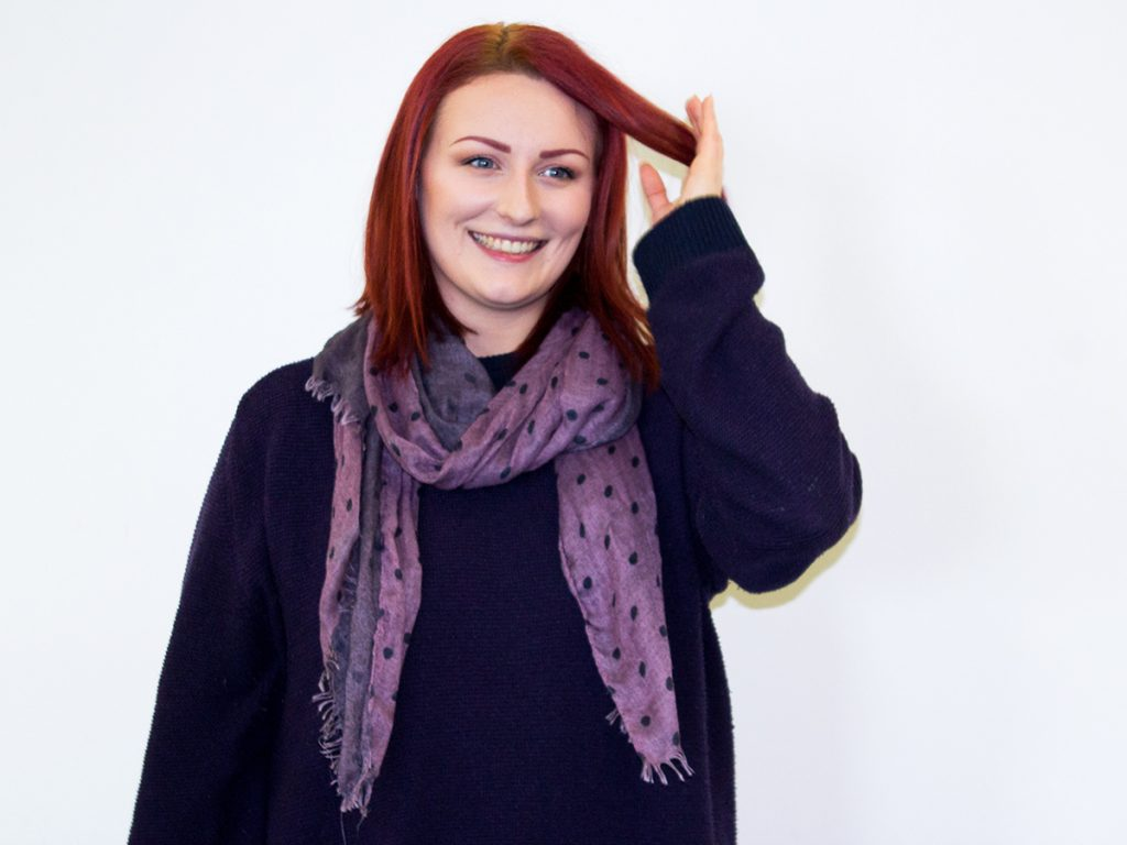Photo of Hazel, who is wearing a purple jumper and a lighter purple scarf stood in front of a white wall. She is smiling at the camera with one hand fiddling with her hair.