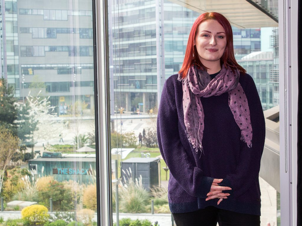 Hazel, who has red shoulder length hair and is wearing a dark purple jumper and a lighter purple scarf is stood in front of a wide window in our MediaCity building. Behind her you can see the communal garden that sits in the middle of MediaCityUK as well as the buildings behind her