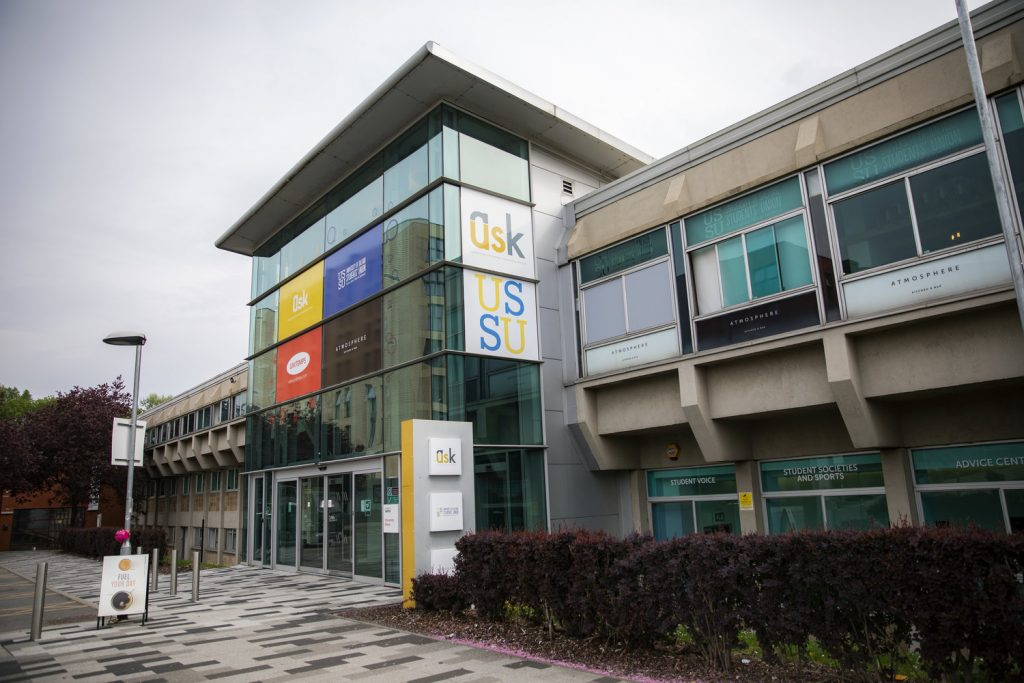 A campus shot of the University House also known as the University of Salfords' Students' Union. There is a row of bushes in front of it, as well as a signboard advertising the starbucks inside. There is also a sign for our AskUS service that has a grey and yellow colour palette.